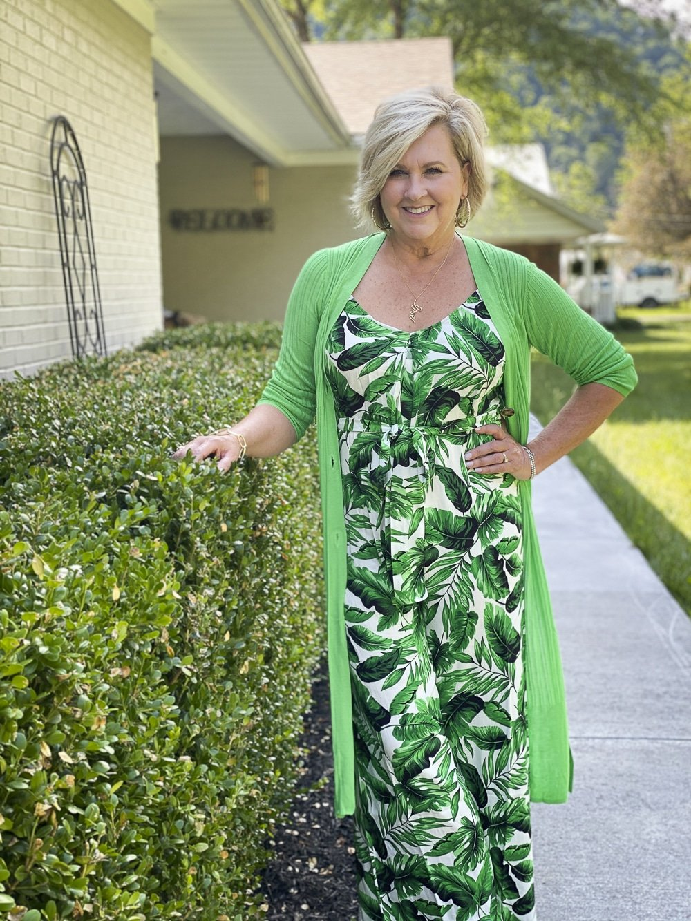 Fashion Blogger 50 Is Not Old is wearing a tropical banana leaf print jumpsuit with a long bright green cardigan from Walmart