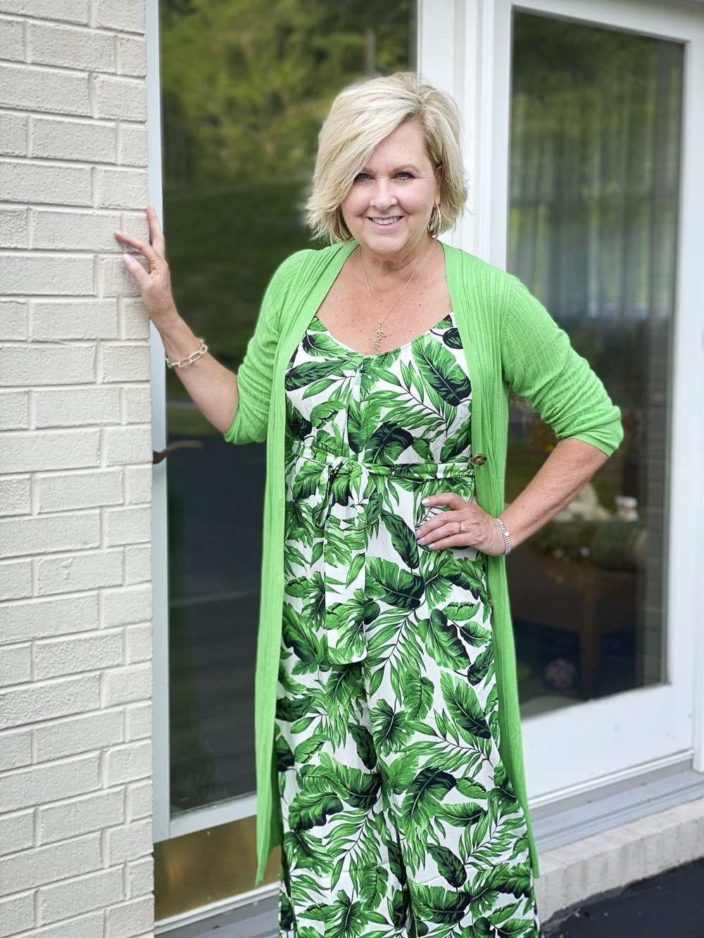 Fashion Blogger 50 Is Not Old is wearing a tropical banana leaf print jumpsuit with a bright green cardigan from Walmart