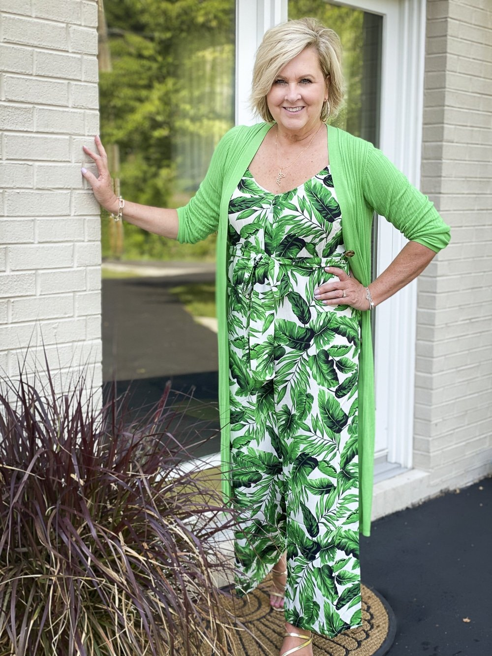 Fashion Blogger 50 Is Not Old is leaning against a door in a tropical banana leaf print jumpsuit with a long bright green cardigan from Walmart