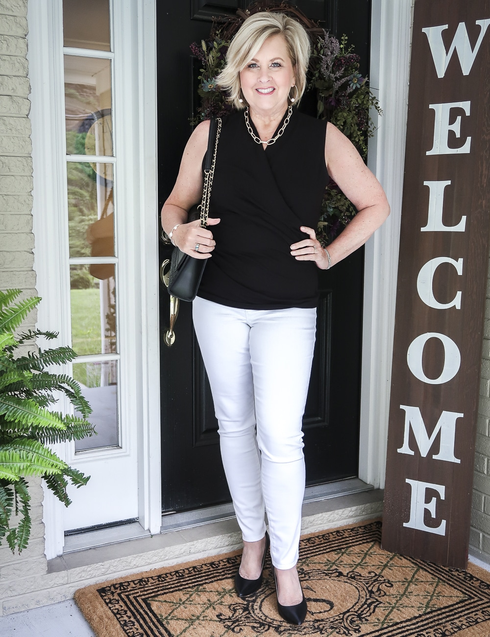 Fashion Blogger 50 Is Not old is wearing a black faux wrap top with white No Stain jeggings, classic black pumps and a black shoulder bag