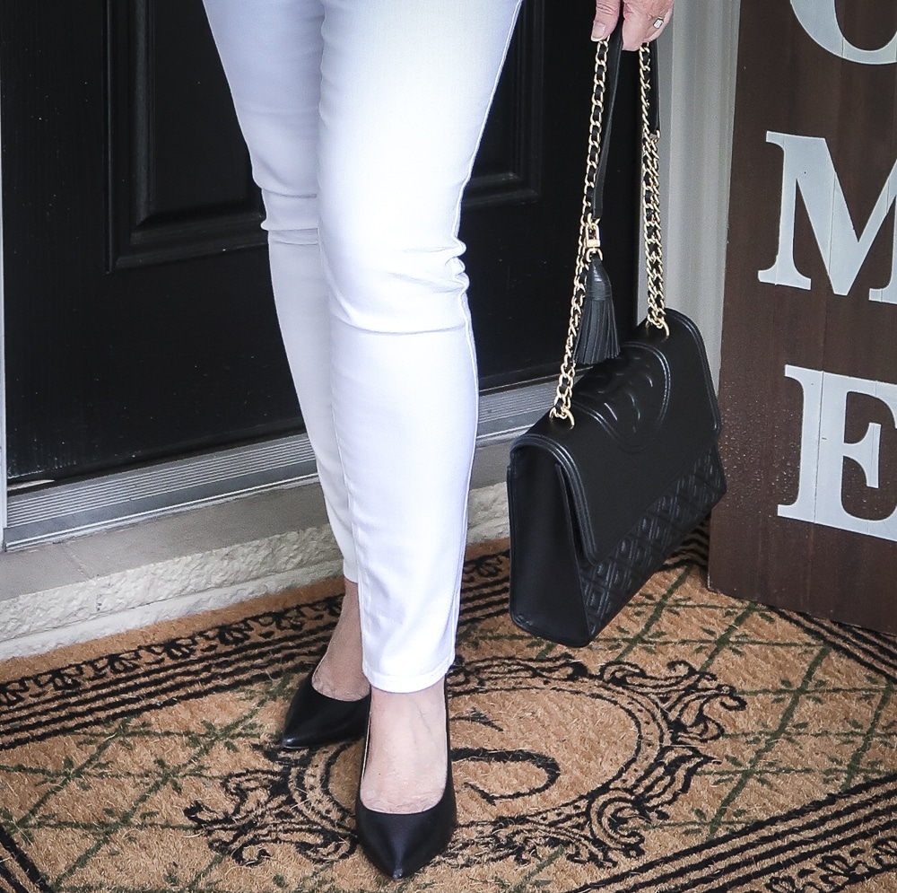 Fashion Blogger 50 Is Not old is wearing white No Stain jeggings, classic black pumps and carrying a black shoulder bag