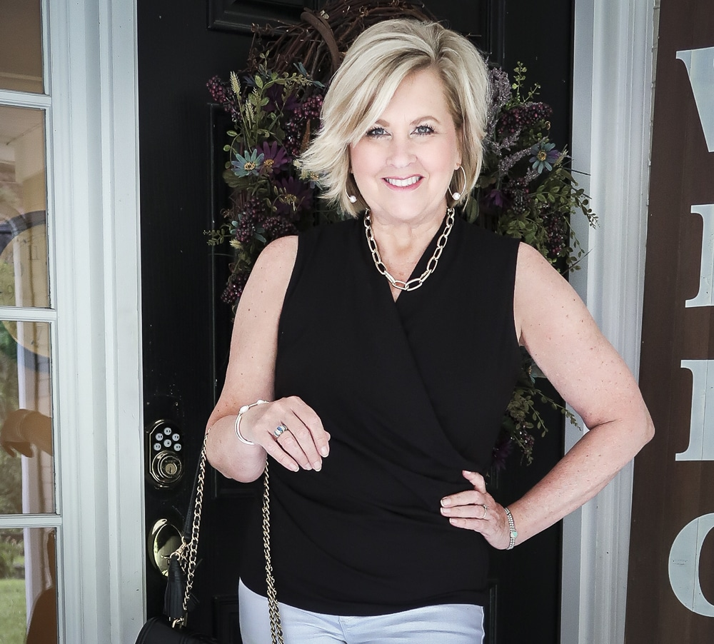 Fashion Blogger 50 Is Not old is wearing a faux wrap top in black