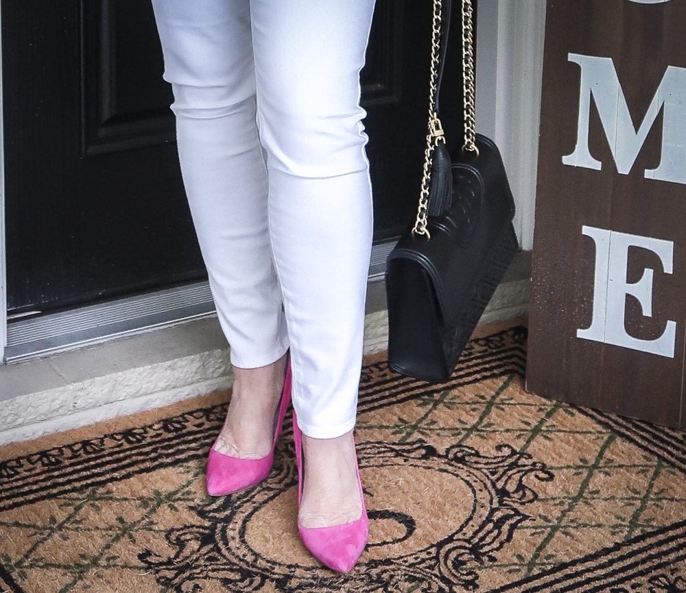 Fashion Blogger 50 Is Not old is wearing white No Stain jeggings, pink pumps and carrying a black shoulder bag