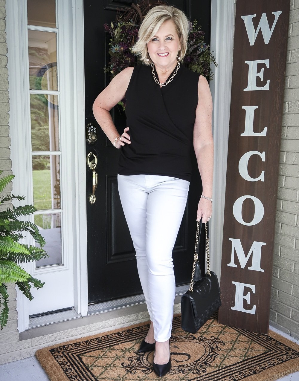 Fashion Blogger 50 Is Not old is wearing a black faux wrap top with white No Stain jeggings, classic black pumps and carrying a black shoulder bag