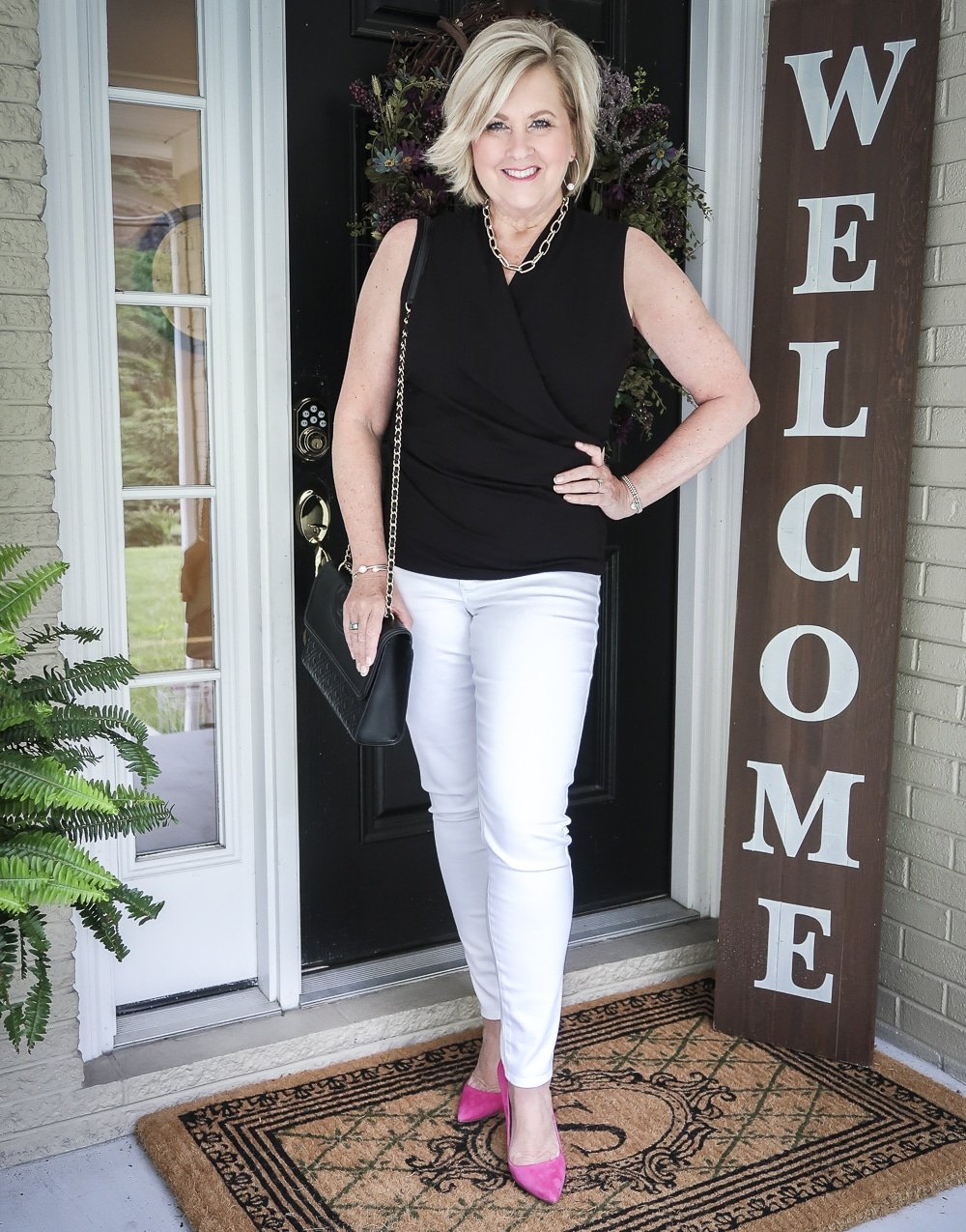 Fashion Blogger 50 Is Not old is wearing a black faux wrap top with white No Stain jeggings, hot pink pumps and carrying a black shoulder bag