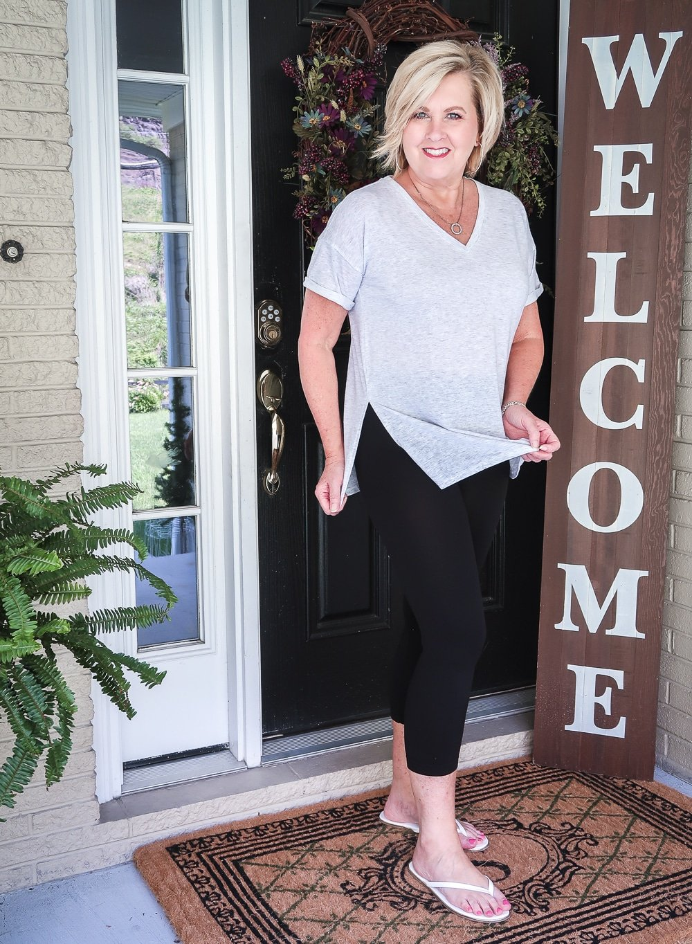 FASHION BLOGGER 50 IS NOT OLD IS WEARING A LIGHT GRAY TUNIC TOP AND BLACK CAPRI LEGGINGS WITH A PAIR OF FLIP FLOPS