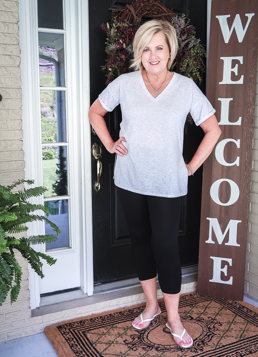 FASHION BLOGGER 50 IS NOT OLD IS WEARING A LIGHT GRAY TOP AND BLACK CAPRI LEGGINGS WITH A PAIR OF WHITE FLIP FLOPS
