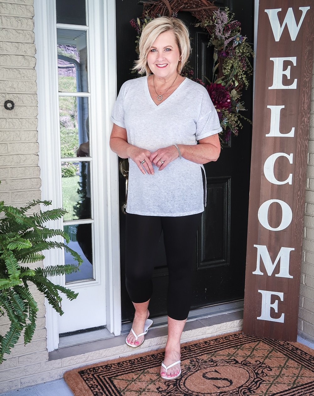 FASHION BLOGGER 50 IS NOT OLD IS WEARING A LIGHT GRAY TUNIC TOP AND BLACK CAPRI LEGGINGS WITH A PAIR OF WHITE FLIP FLOPS