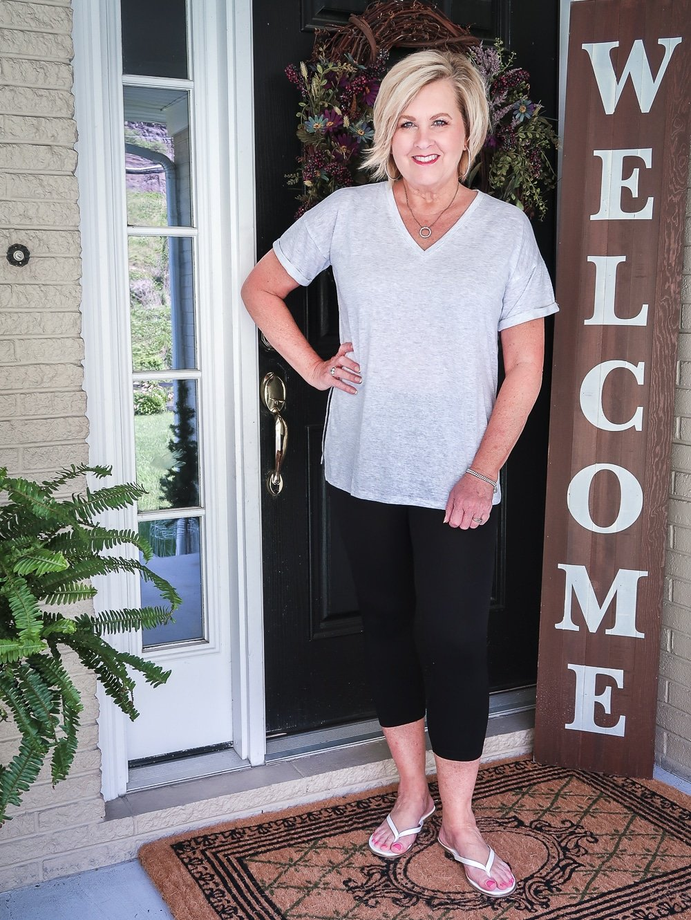 FASHION BLOGGER 50 IS NOT OLD IS WEARING A LIGHT GRAY TUNIC TOP AND BLACK LEGGINGS WITH A PAIR OF WHITE FLIP FLOPS