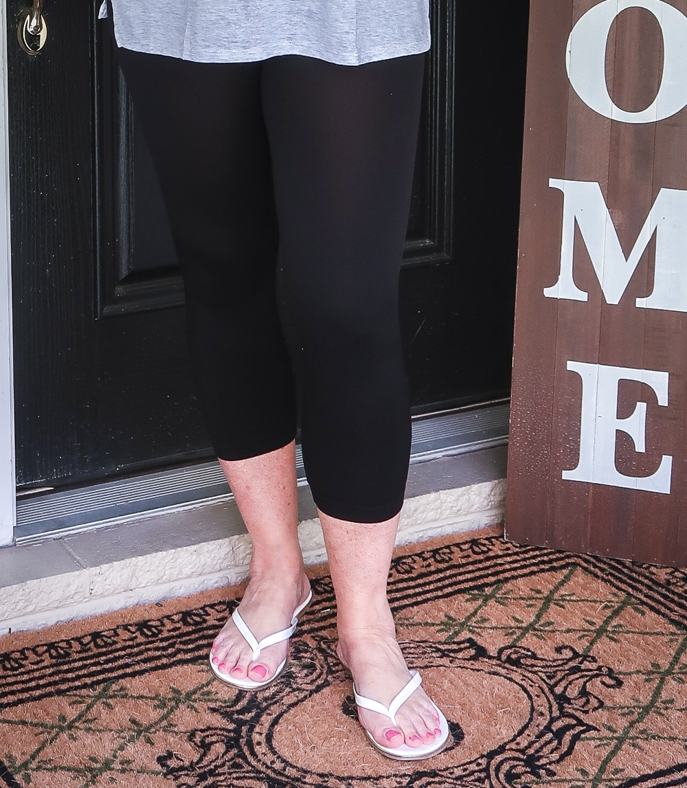 FASHION BLOGGER 50 IS NOT OLD IS WEARING BLACK CAPRI LEGGINGS WITH A PAIR OF WHITE FLIP FLOPS
