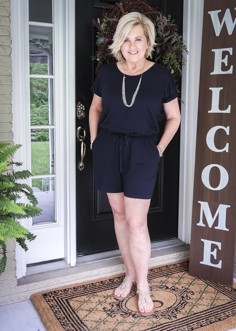 Fashion Blogger 50 Is Not Old is wearing a cute navy romper with gold braided sandals and gold jewelry