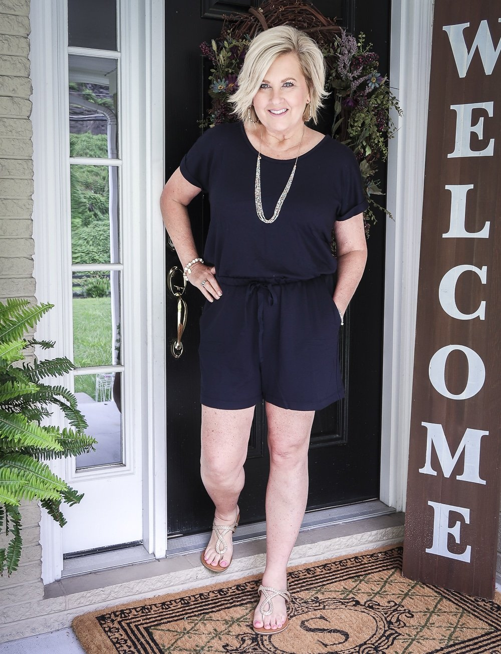 Fashion Blogger 50 Is Not Old is wearing a cute navy romper from Loft with gold braided sandals and gold jewelry