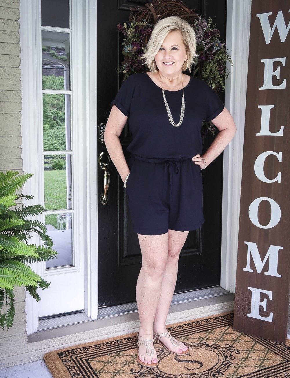 Fashion Blogger 50 Is Not Old is wearing a navy romper with gold braided sandals and gold jewelry