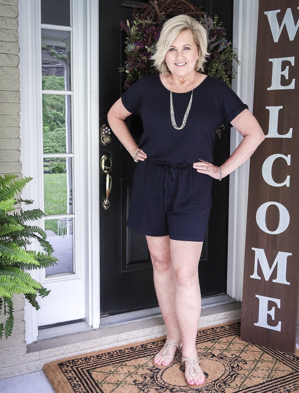 Fashion Blogger 50 Is Not Old is wearing a cute navy romper, gold braided sandals, and gold jewelry