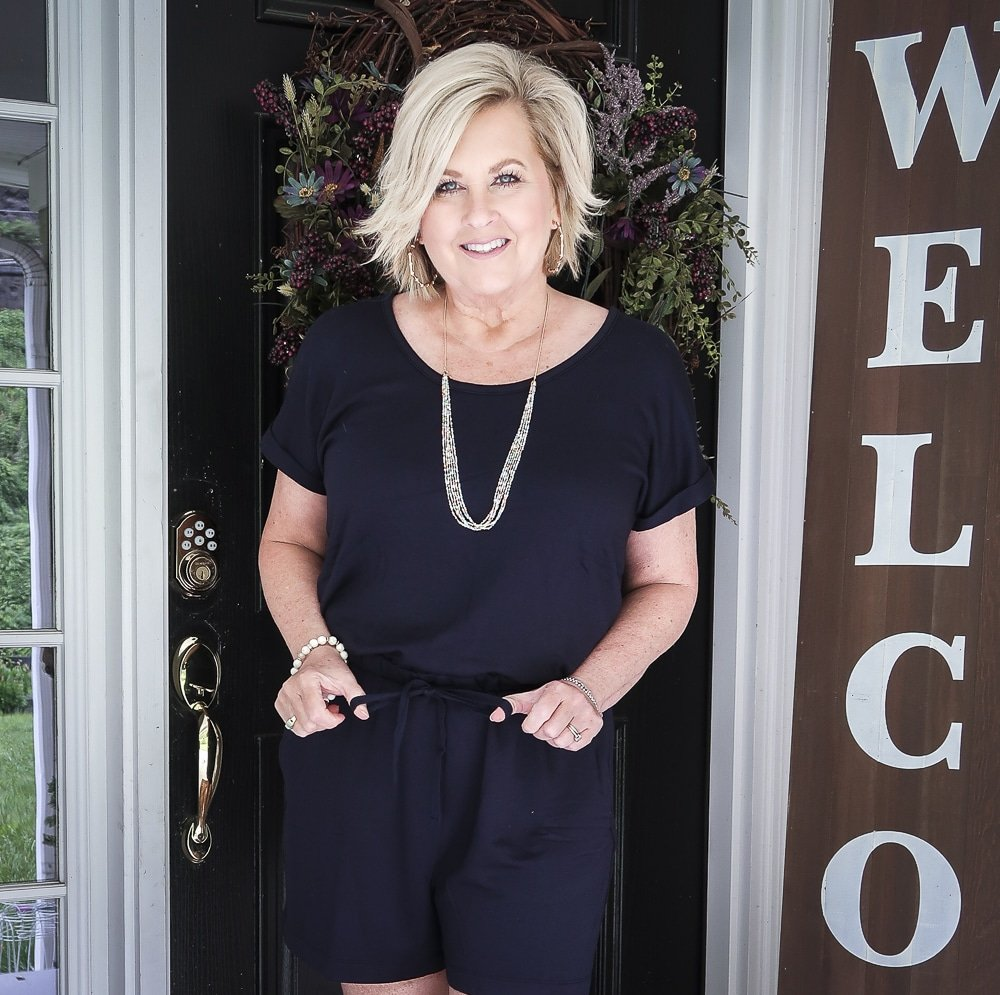 Fashion Blogger 50 Is Not Old is wearing a cute navy romper from Loft and gold jewelry