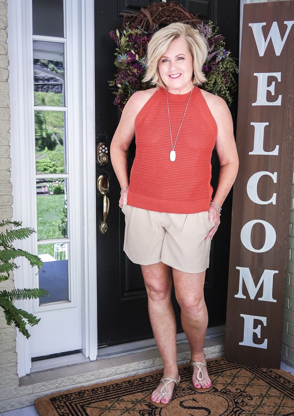 Fashion Blogger 50 Is Not Old is wearing a red clay crochet top, gold jewelry, beige linen shorts, and gold sandals
