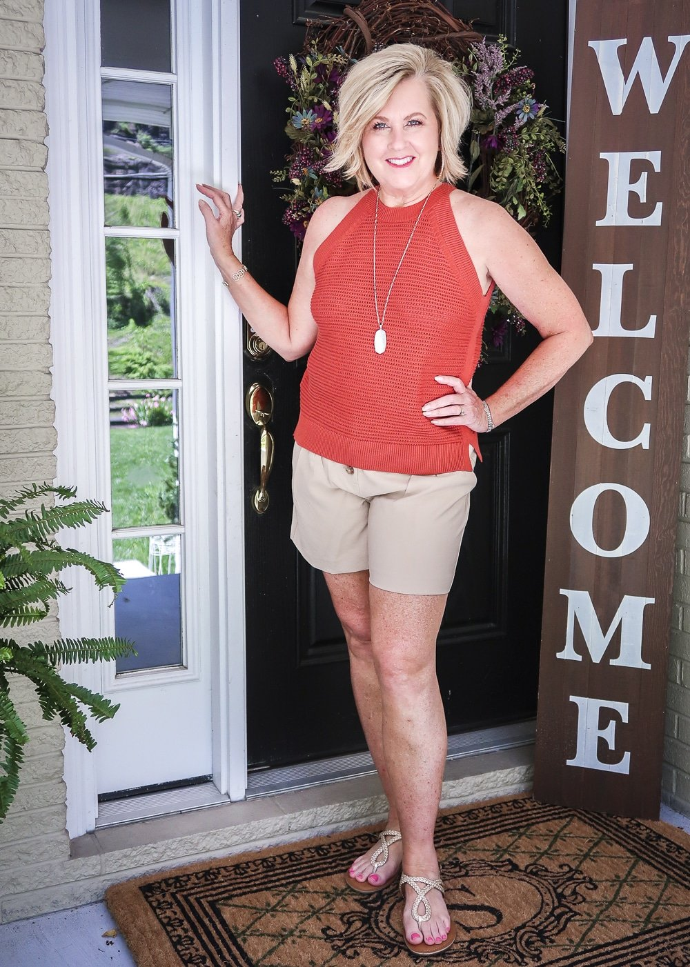Fashion Blogger 50 Is Not Old is wearing a red clay crochet halter top, gold jewelry, beige linen shorts, and gold sandals