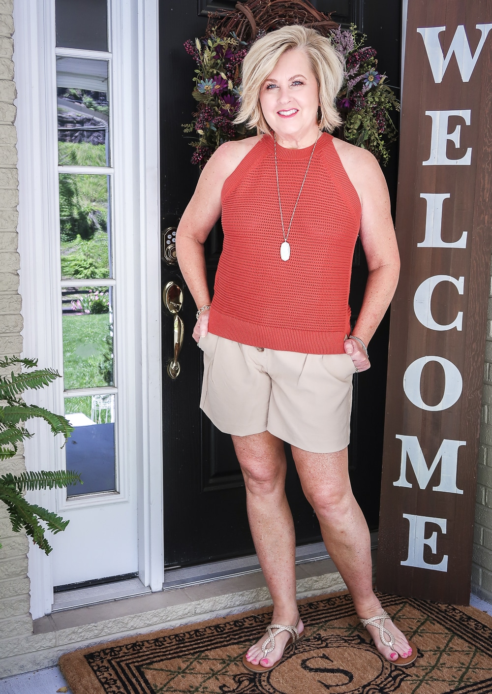Fashion Blogger 50 Is Not Old is wearing a red clay crochet halter top, gold jewelry, beige shorts, and gold sandals