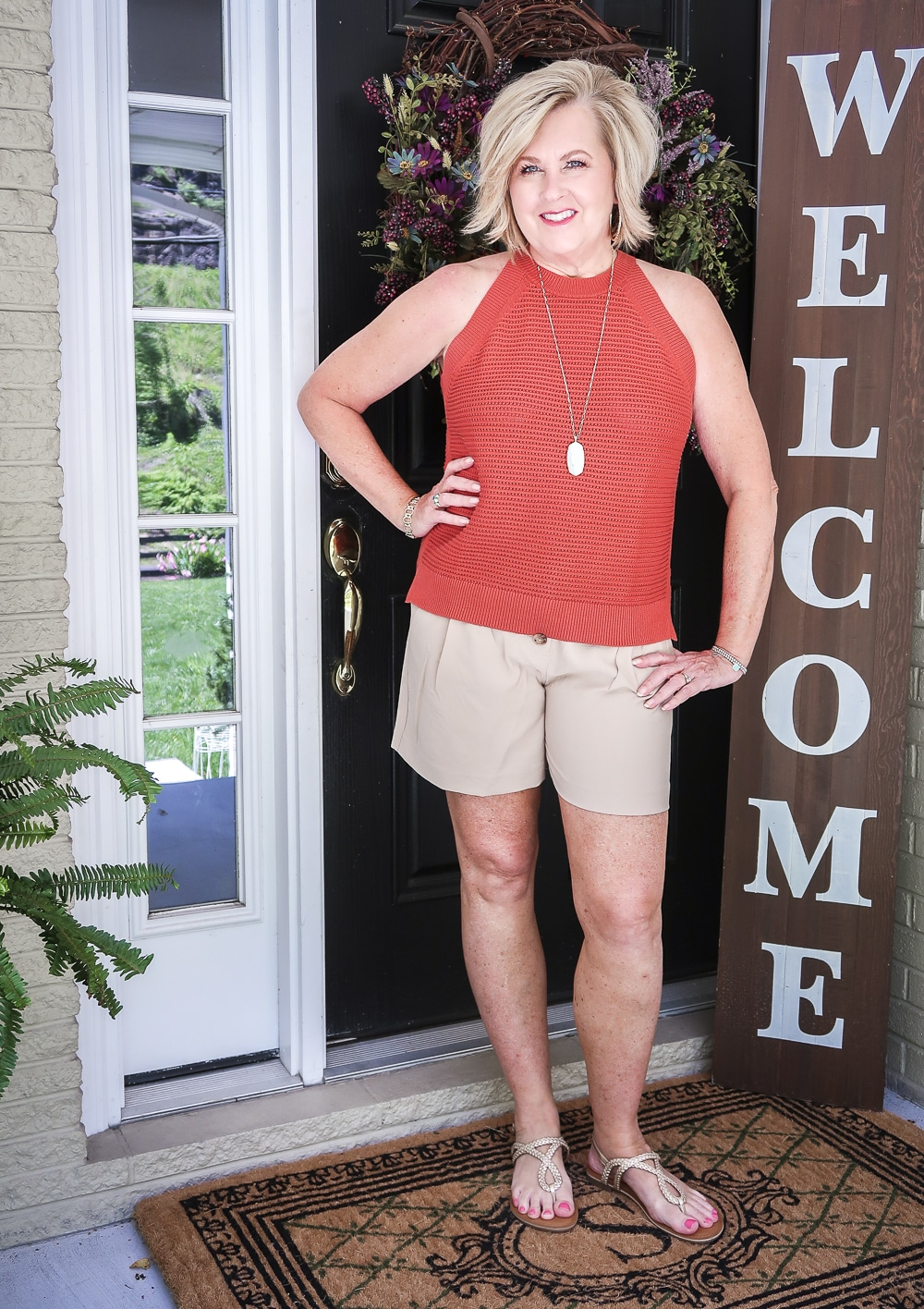 Fashion Blogger 50 Is Not Old is wearing a red clay crochet halter top, beige linen shorts, and gold sandals