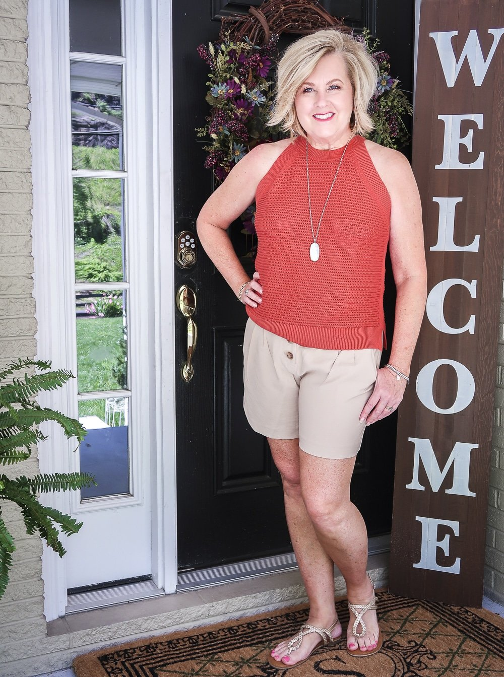 Fashion Blogger 50 Is Not Old is wearing a red clay crochet halter top, gold jewelry, linen shorts, and gold sandals