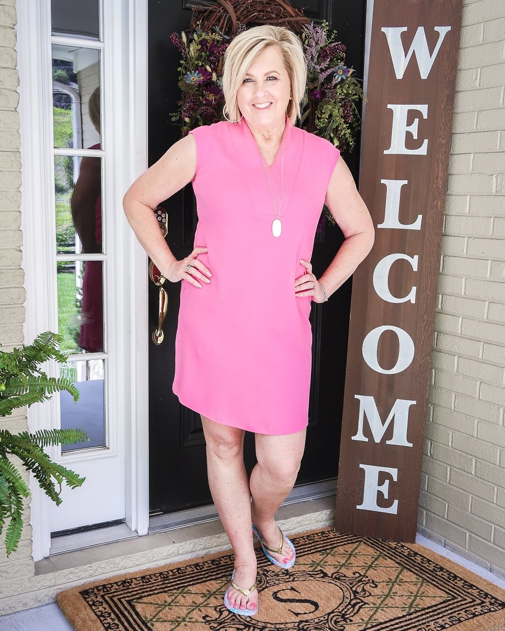Fashion Blogger 50 Is Not Old is wearing a pink sheath dress with Lilly Pulitzer flip flops