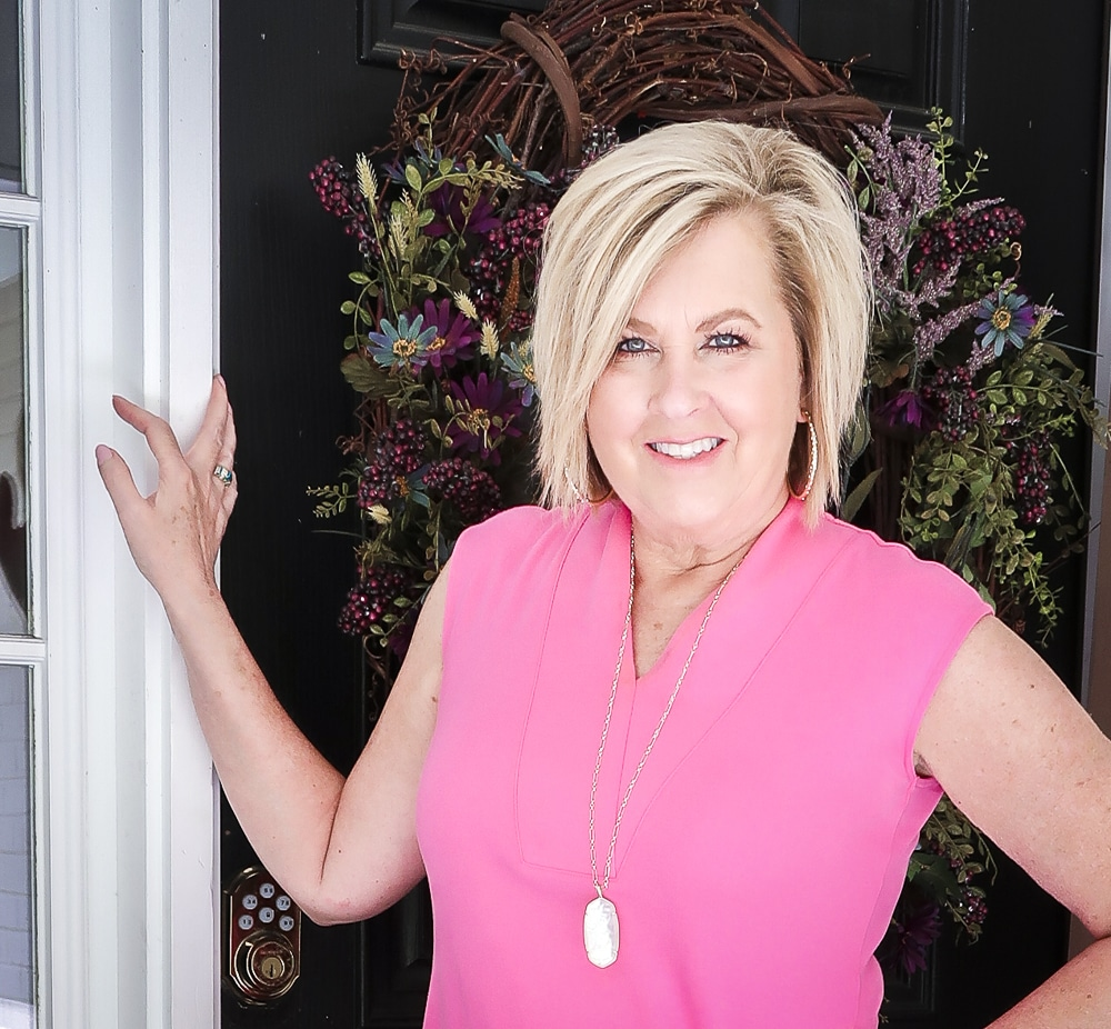 Fashion Blogger 50 Is Not Old is wearing a pink sheath dress with gold jewelry