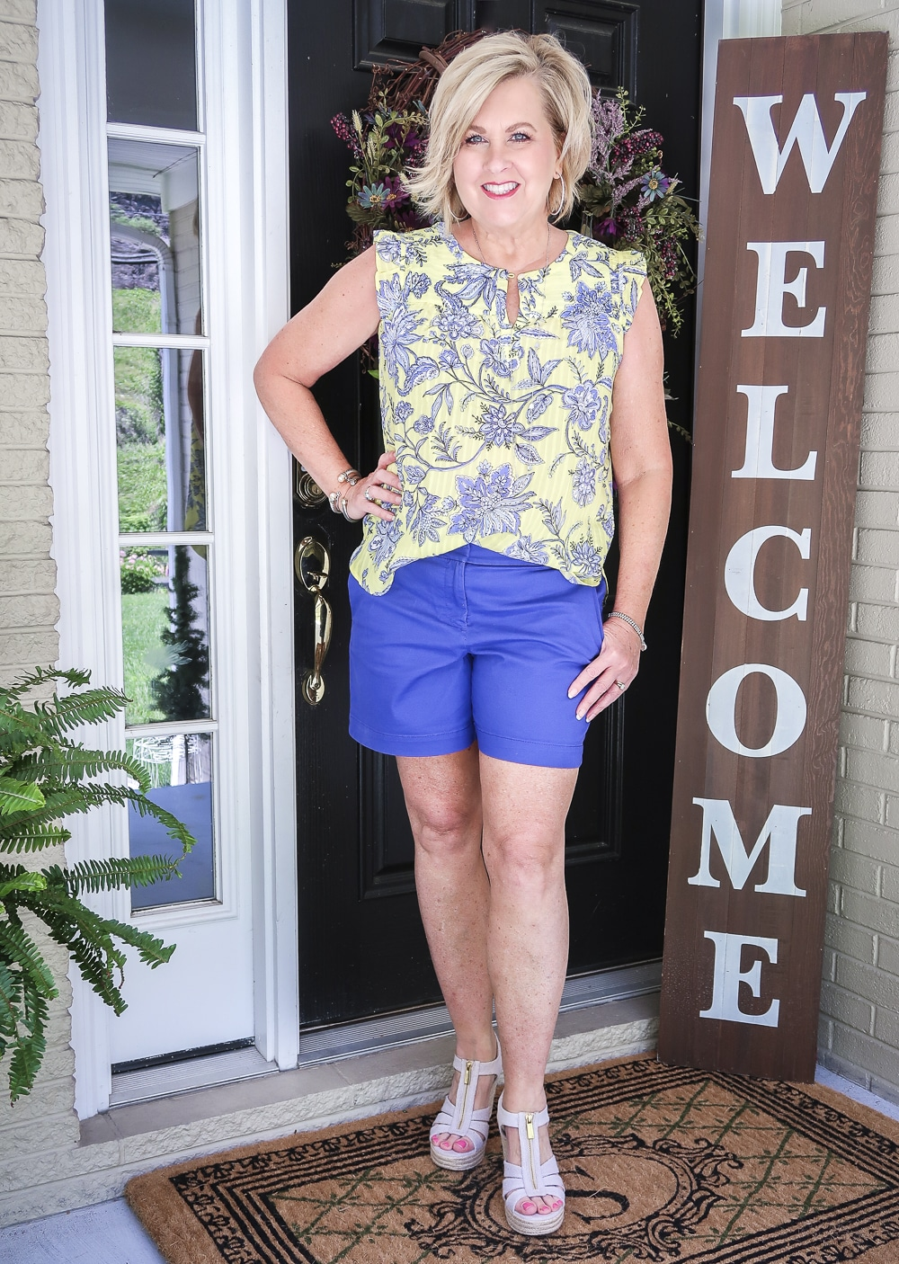 Fashion Blogger 50 Is Not Old wearing a yellow top with a blue floral design, blue shorts, and platform espadrille wedge shoes by Micheal Kors