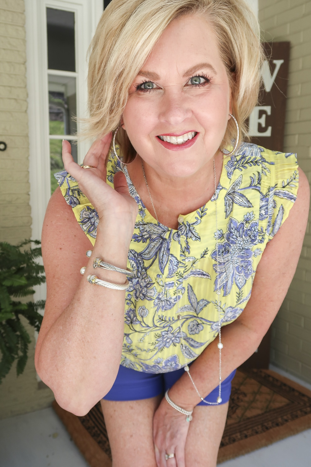 Fashion Blogger 50 Is Not Old wearing a yellow top with a blue floral design and silver jewelry