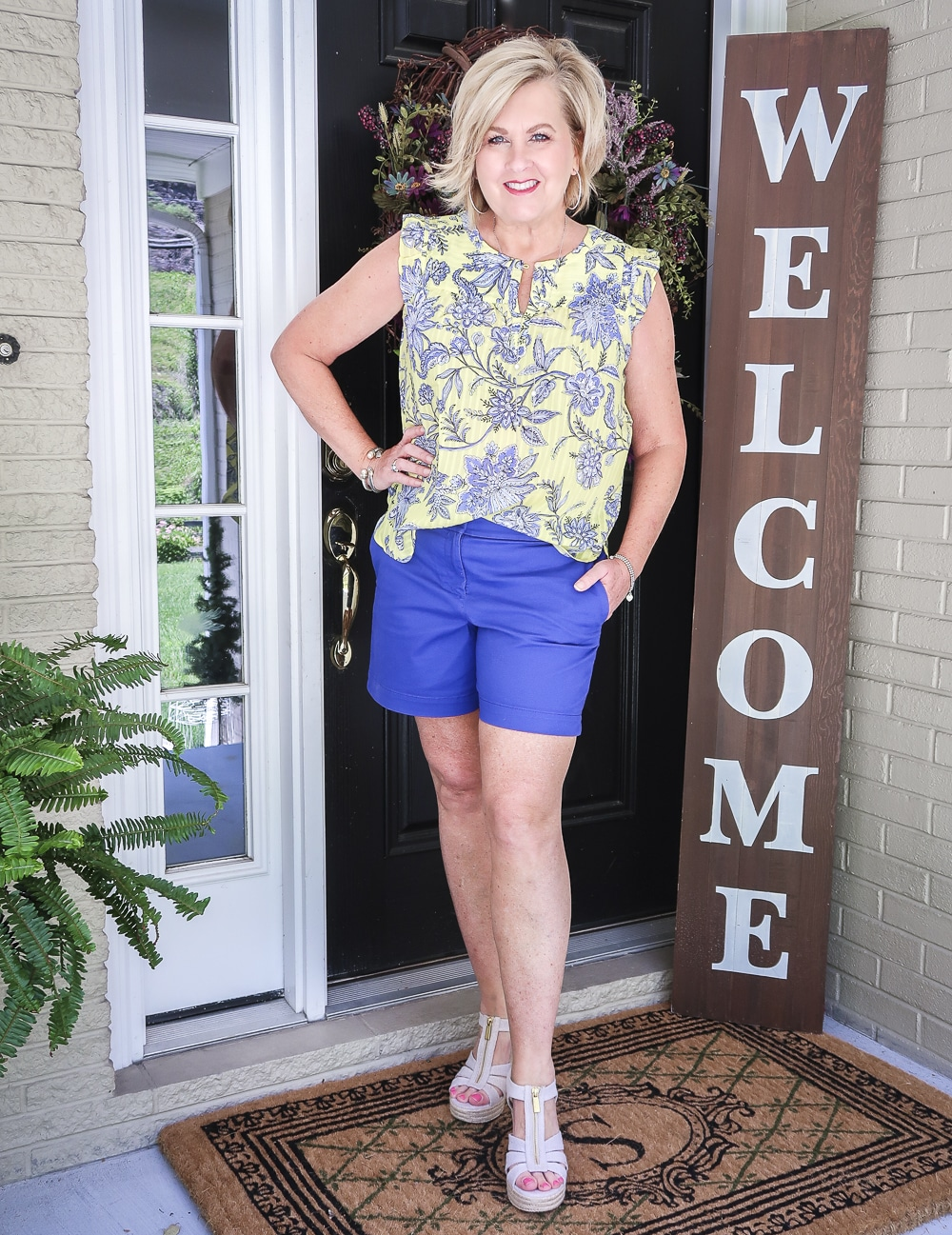 Fashion Blogger 50 Is Not Old wearing a yellow top with a blue floral design, azure blue shorts, and platform espadrille wedge shoes by Micheal Kors