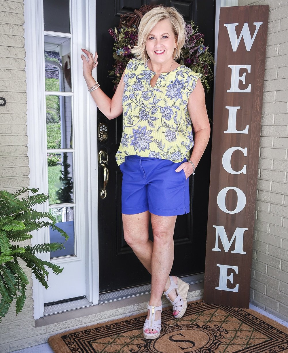 Fashion Blogger 50 Is Not Old wearing a yellow top with a blue floral design, azure blue shorts, and platform espadrille wedge shoes