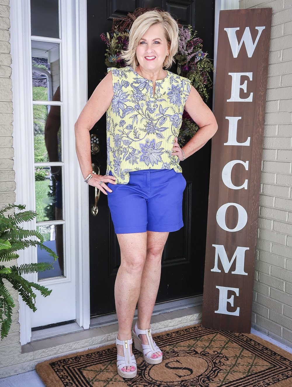 Fashion Blogger 50 Is Not Old wearing a yellow top with a floral design, azure blue shorts, and platform espadrille wedge shoes by Micheal Kors