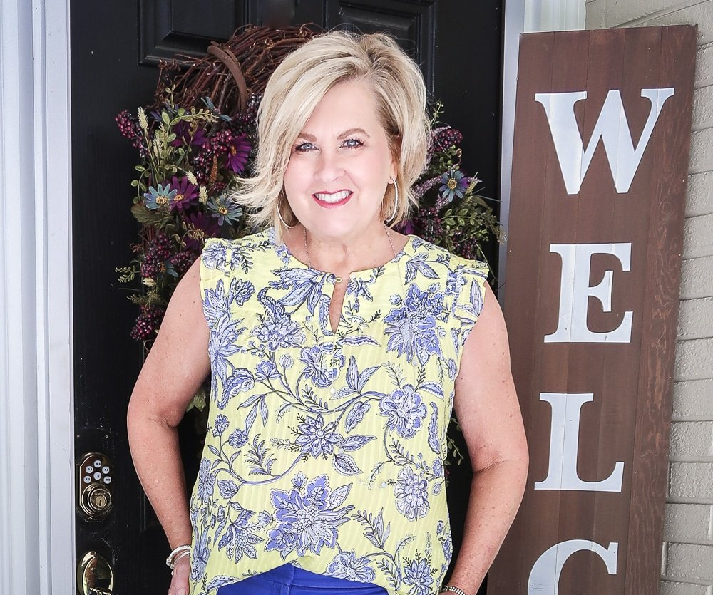 Fashion Blogger 50 Is Not Old wearing a yellow top with a blue design