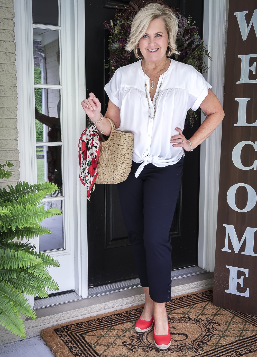 Fashion Blogger 50 Is Not Old is wearing a white tie-front top with navy blue crop pants, red espadrille shoes, and a straw tote with a scarf tied on the handle