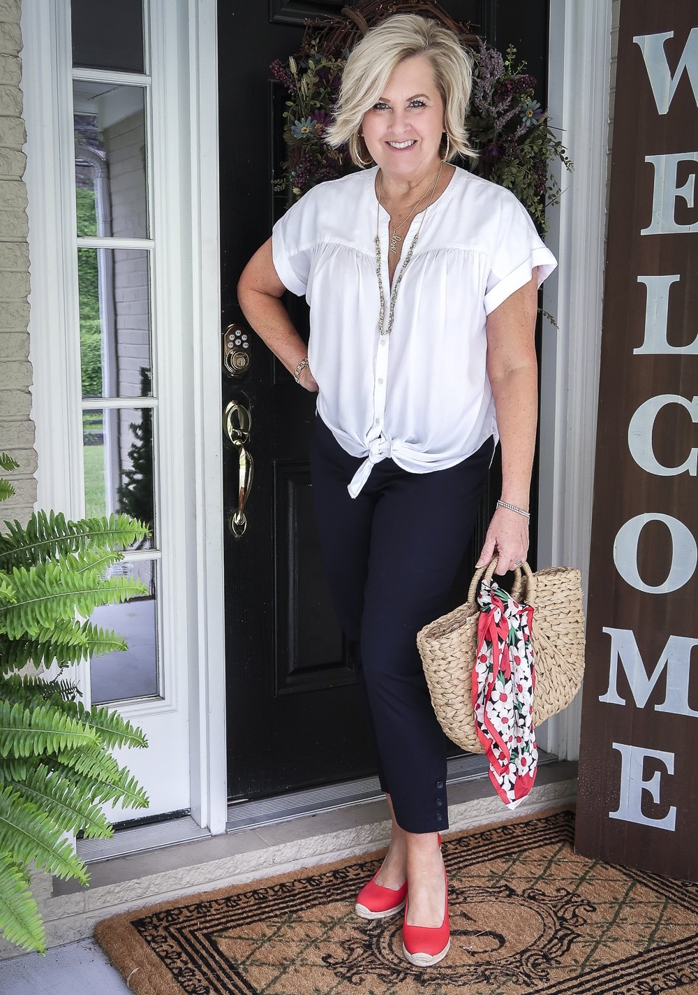 Fashion Blogger 50 Is Not Old is wearing a white tie-front top with navy blue crop pants, red espadrille shoes, and a straw tote with a scarf on the hand