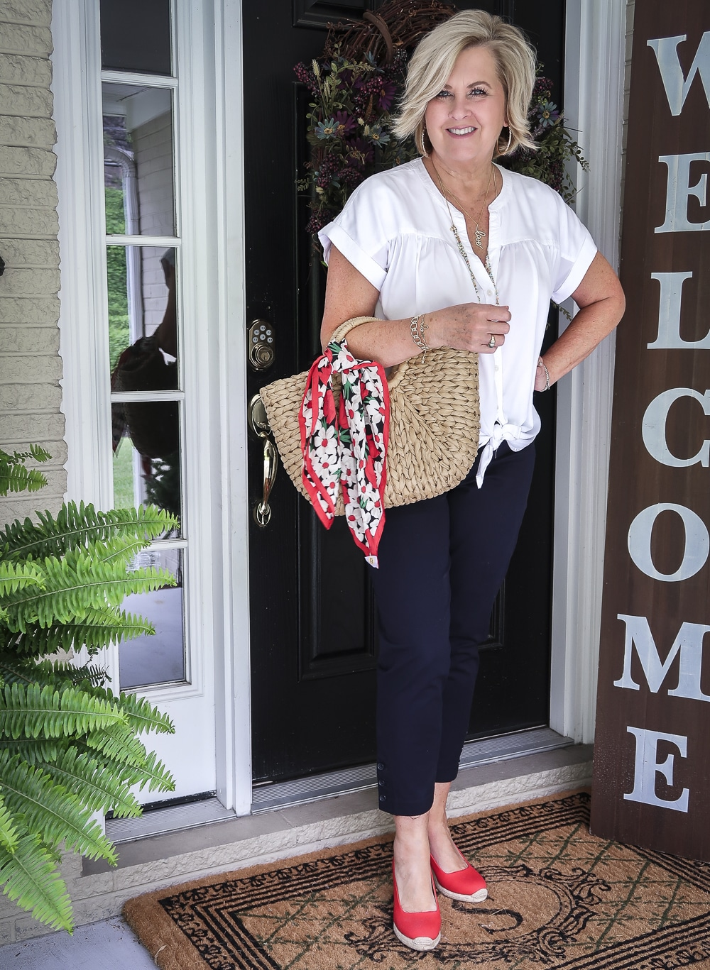 Fashion Blogger 50 Is Not Old is wearing a white tie-front top with navy crop pants, red espadrille shoes, and a straw tote with a scarf tied on the hand