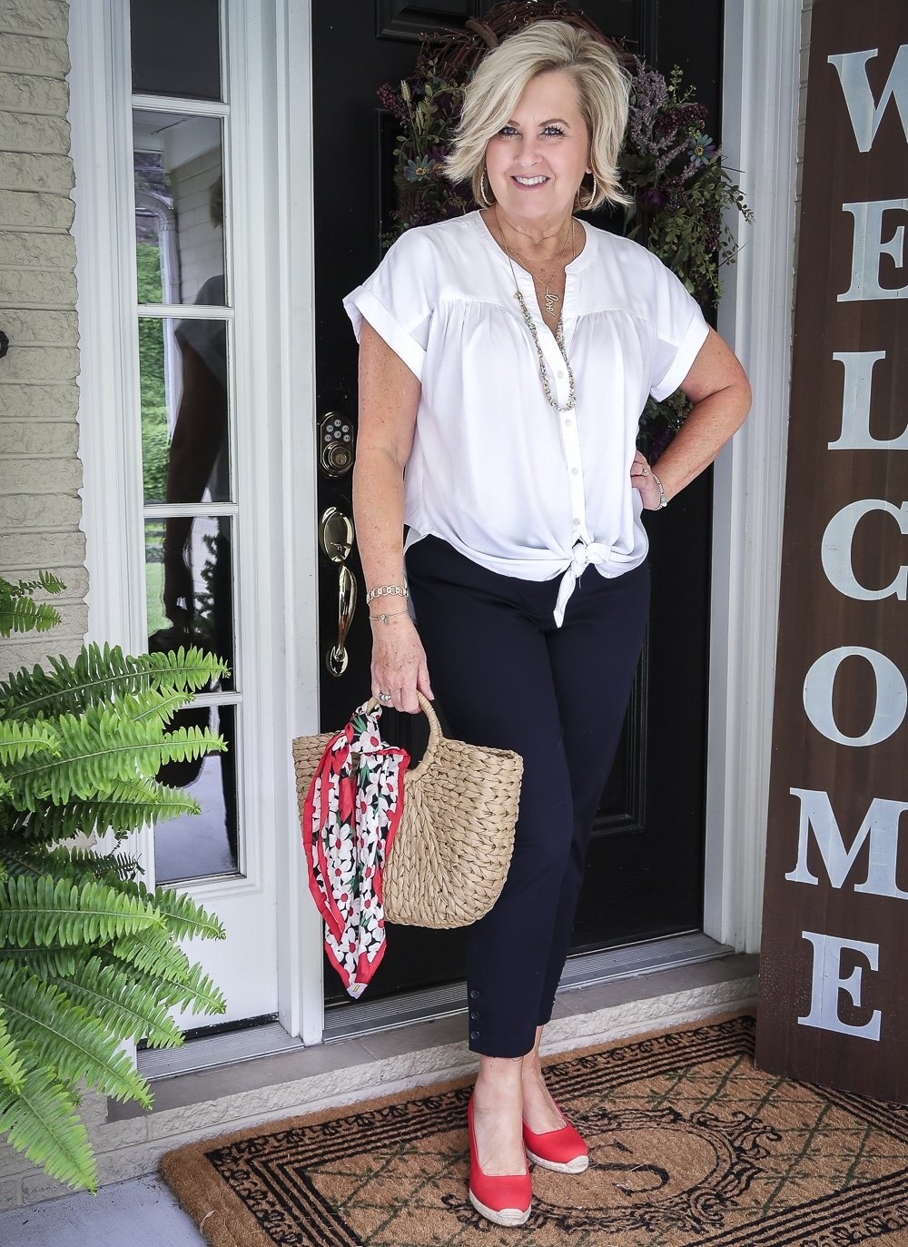 Fashion Blogger 50 Is Not Old is wearing a white tie-front top with blue crop pants, red espadrille shoes, and a straw tote with a scarf tied on the hand