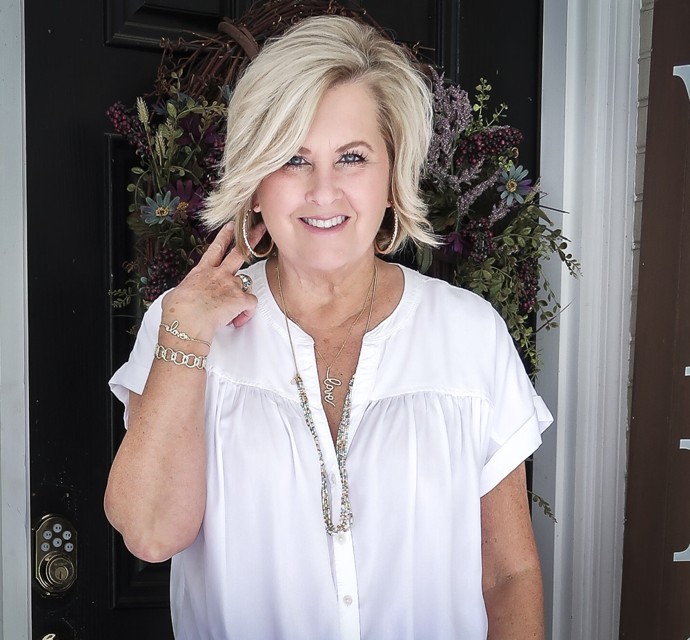 Fashion Blogger 50 Is Not Old is wearing a white tie-front top with gold jewelry