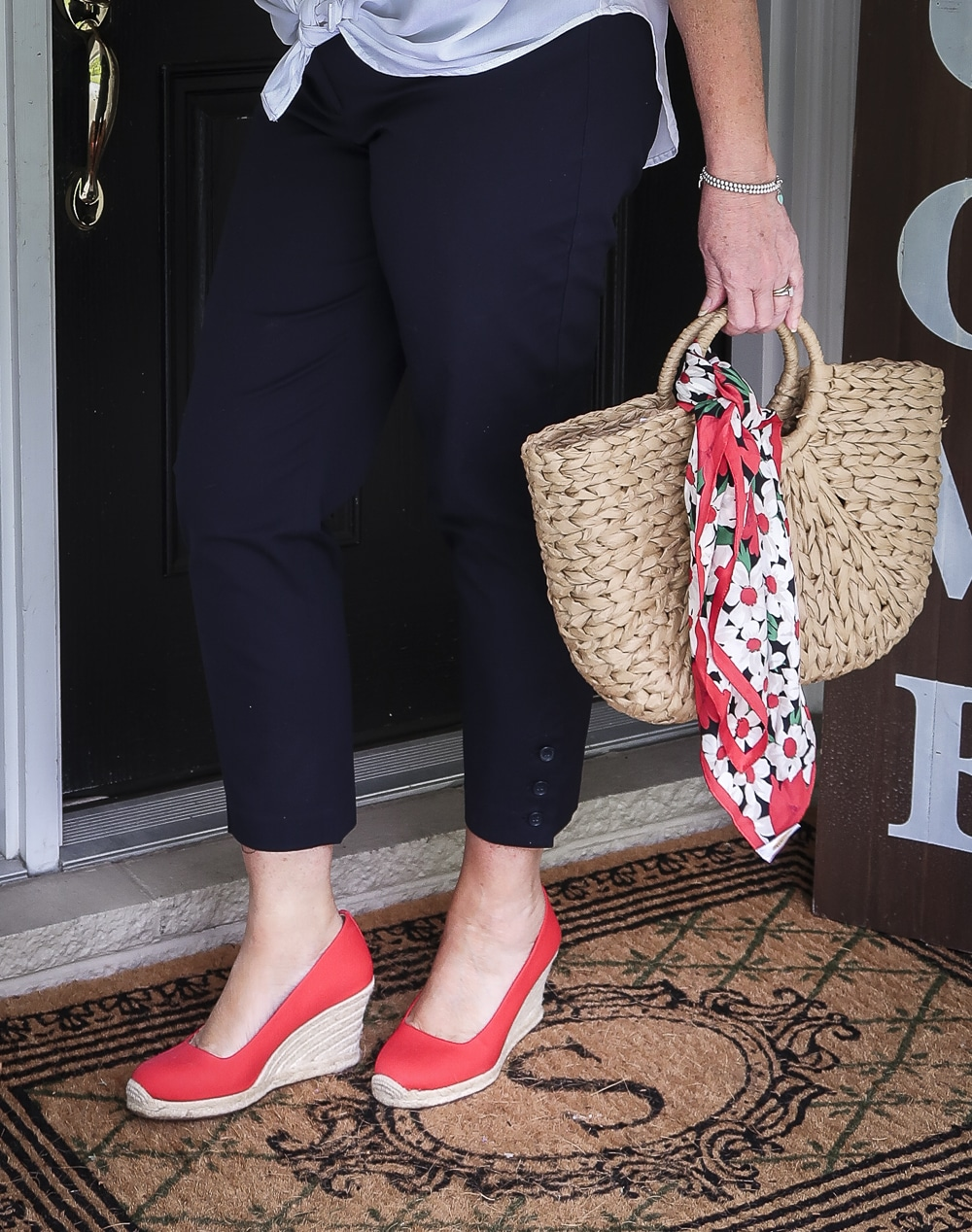 Fashion Blogger 50 Is Not Old is wearing navy blue crop pants, red espadrille shoes, and a straw tote with a scarf tied on the hand