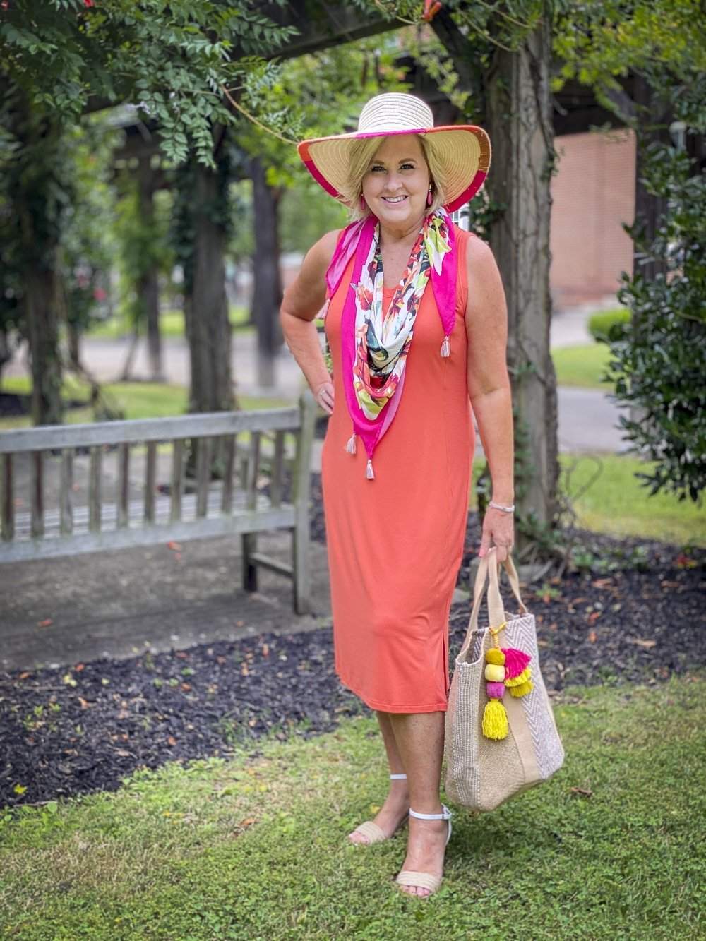 Fashion Blogger 50 Is Not Old is wearing an orange midi dress with a tropical print scarf in pink, a yarn trimmed straw hat, and carrying a jute tote with colorful pompoms all from Chico's
