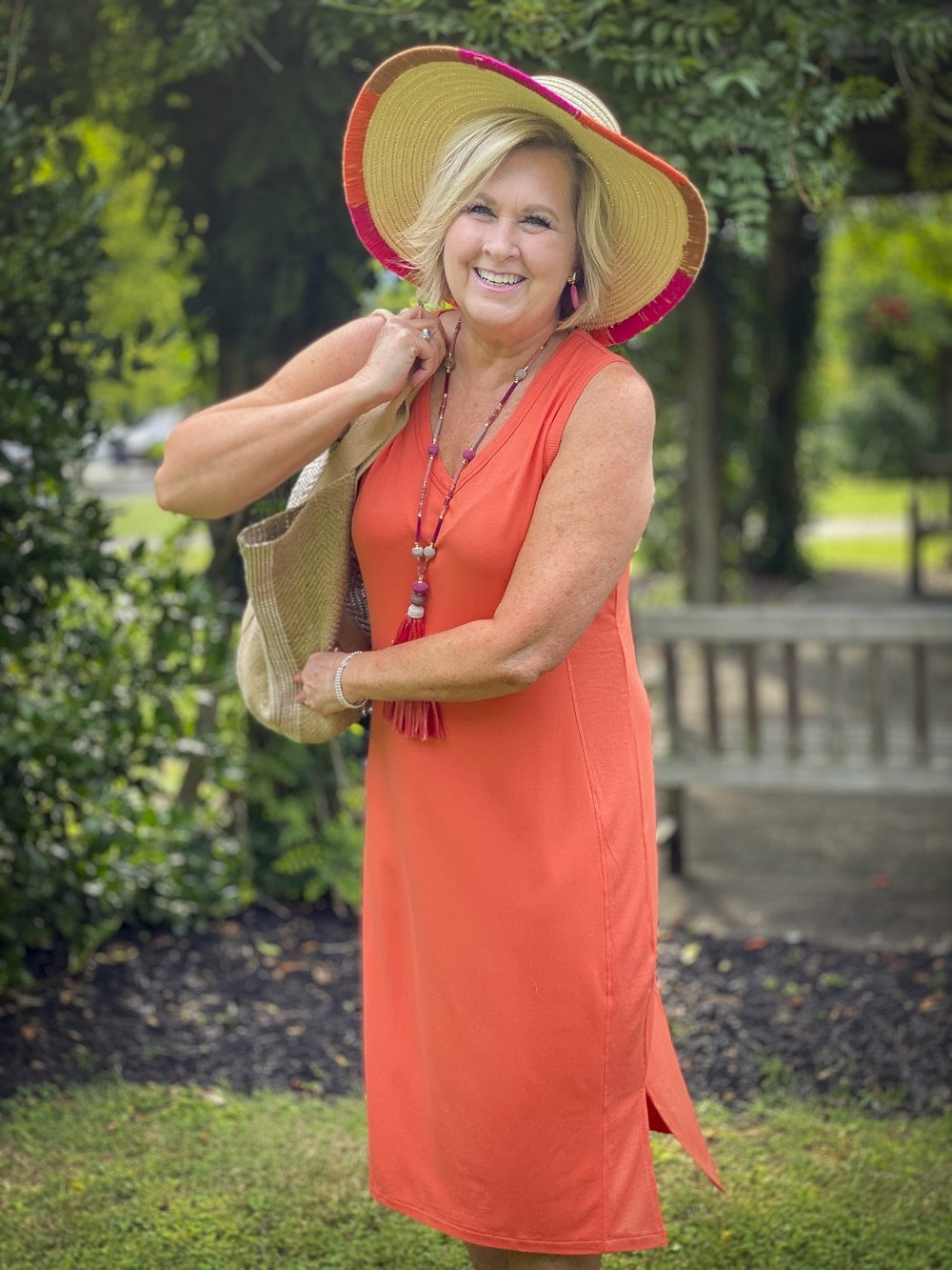 Fashion Blogger 50 Is Not Old is wearing an orange midi dress with a tassel necklace in pink, a yarn trimmed straw hat, and carrying a jute tote all from Chico's