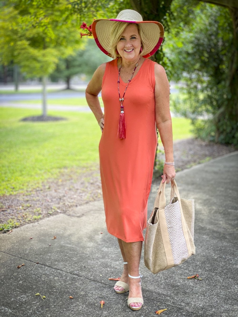 Fashion Blogger 50 Is Not Old is wearing an orange midi dress with a summerberry tassel necklace in pink, a yarn trimmed straw hat, and carrying a jute tote all from Chico's