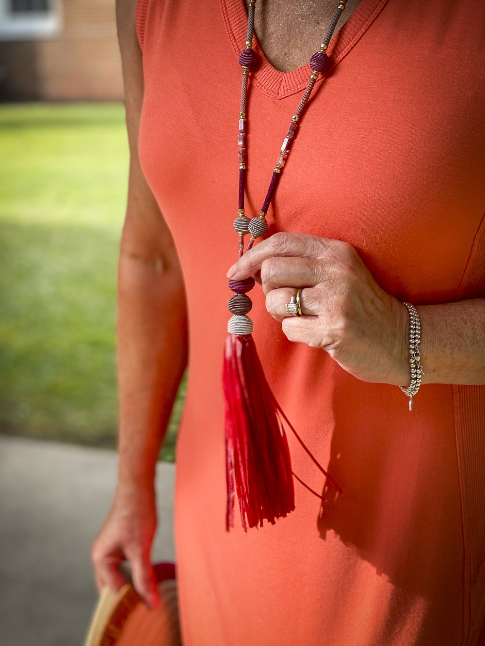 Fashion Blogger 50 Is Not Old is wearing an orange midi dress with a summerberry tassel necklace in pink all from Chico's