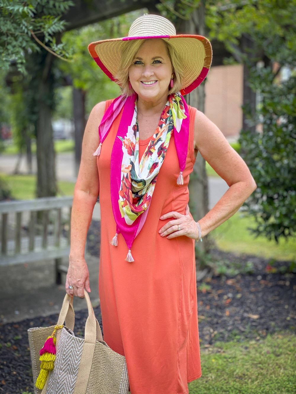 Fashion Blogger 50 Is Not Old is wearing an orange midi dress with a tropical print scarf in pink, a yarn trimmed straw hat, and carrying a jute tote all from Chico's
