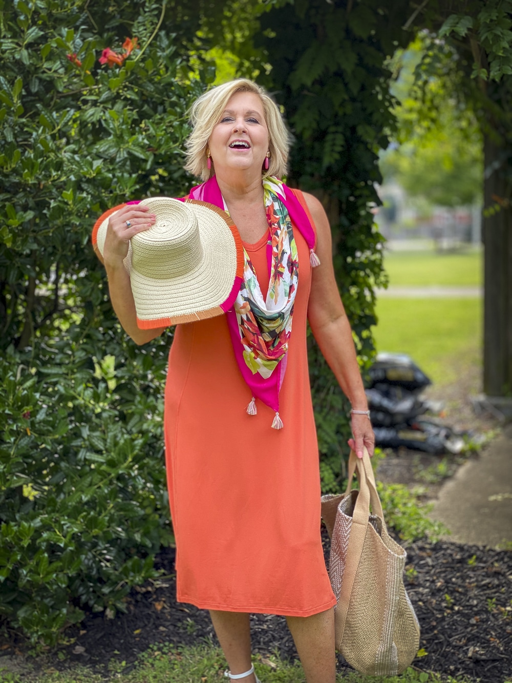 Fashion Blogger 50 Is Not Old is wearing an orange midi dress with a tropical print scarf, a yarn trimmed straw hat, and carrying a jute tote all from Chico's