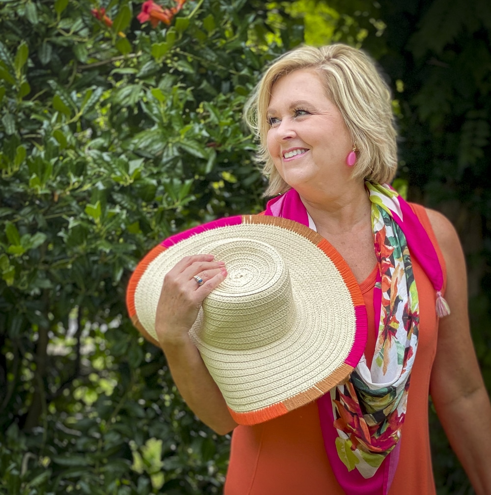 Fashion Blogger 50 Is Not Old is wearing an orange midi dress with a tropical print scarf in pink, a yarn trimmed straw hat, and berry pink earrings all from Chico's