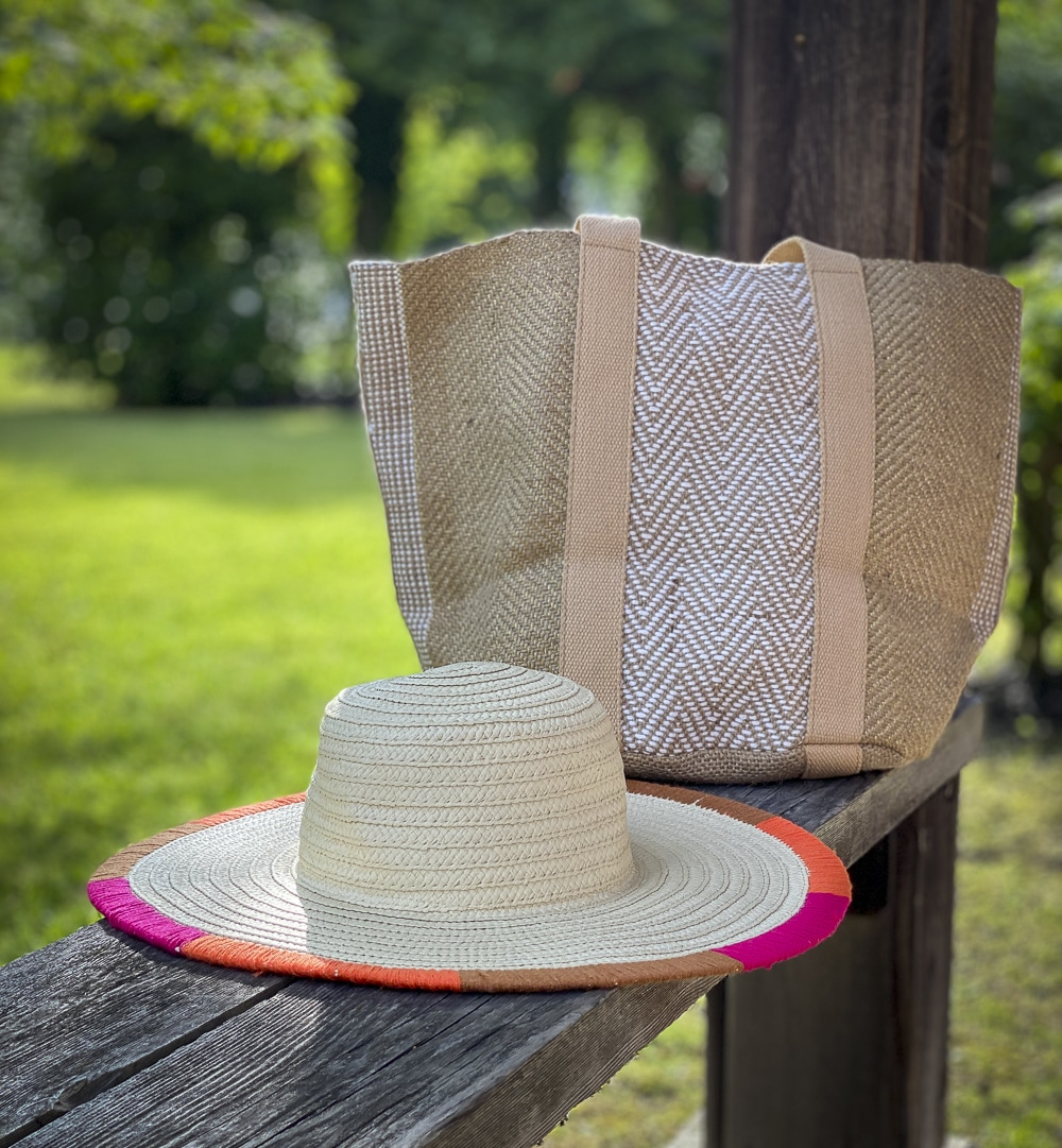 Fashion Blogger 50 Is Not Old is showing a yarn trimmed straw hat, and carrying a jute tote all from Chico's
