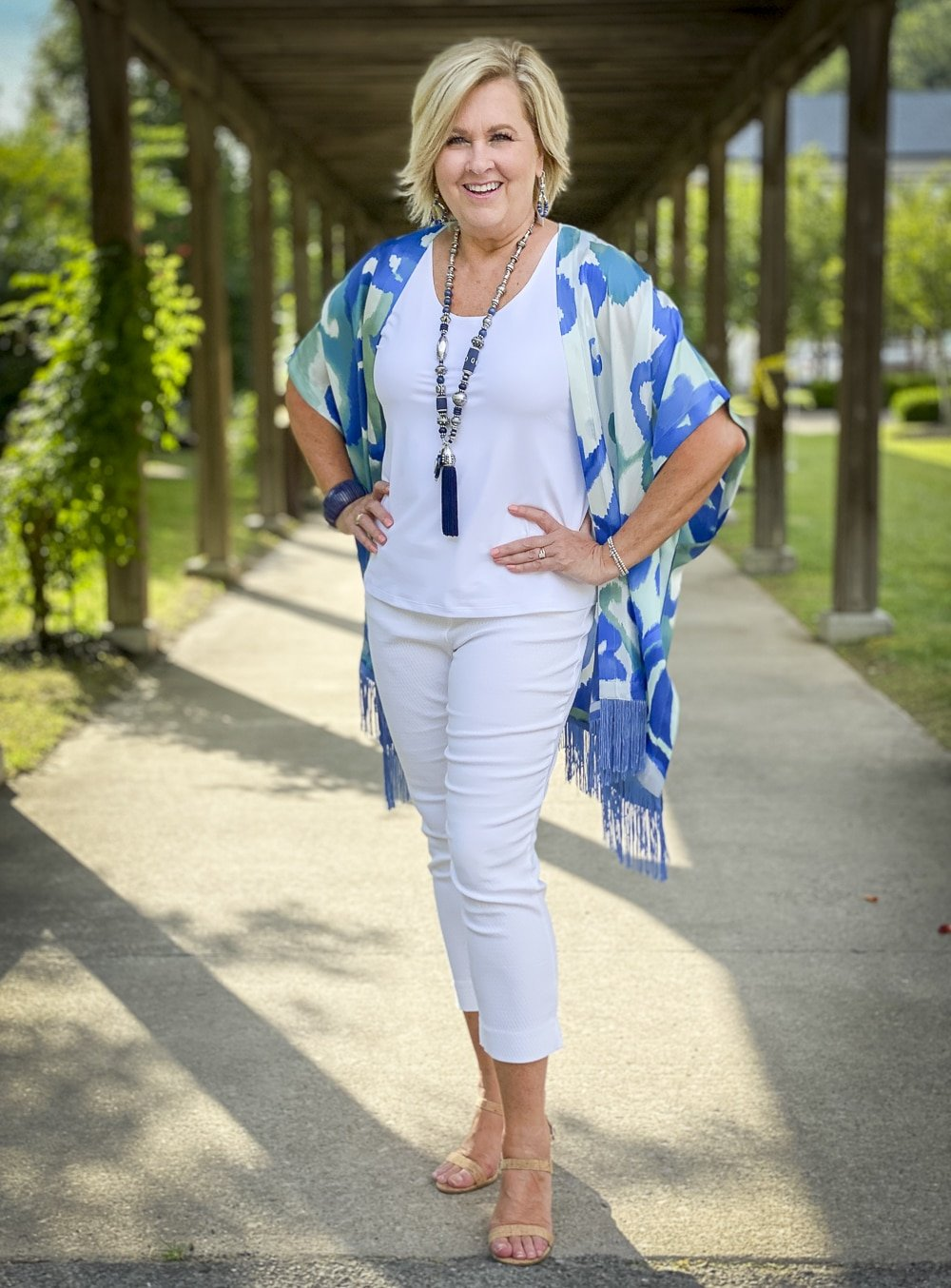 Fashion Blogger 50 Is Not Old is wearing a white tank top, white textured crop pants, and a colorful silk ruana from Chicos with a long navy necklace and bamboo heels