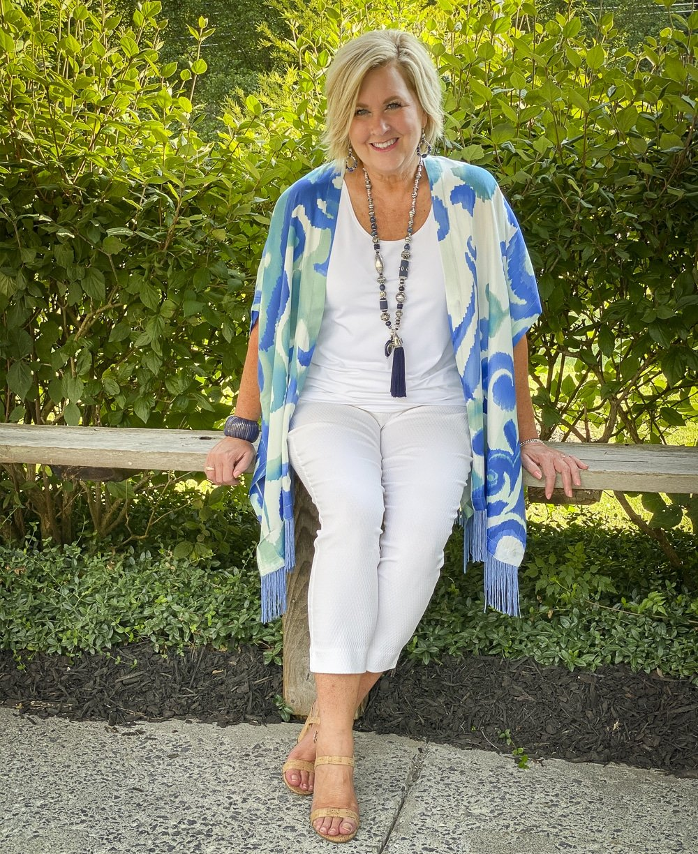 Fashion Blogger 50 Is Not Old is sitting down on a bench wearing a white tank top, white textured crop pants, and a colorful silk ruana from Chicos with a long navy necklace and bamboo heels
