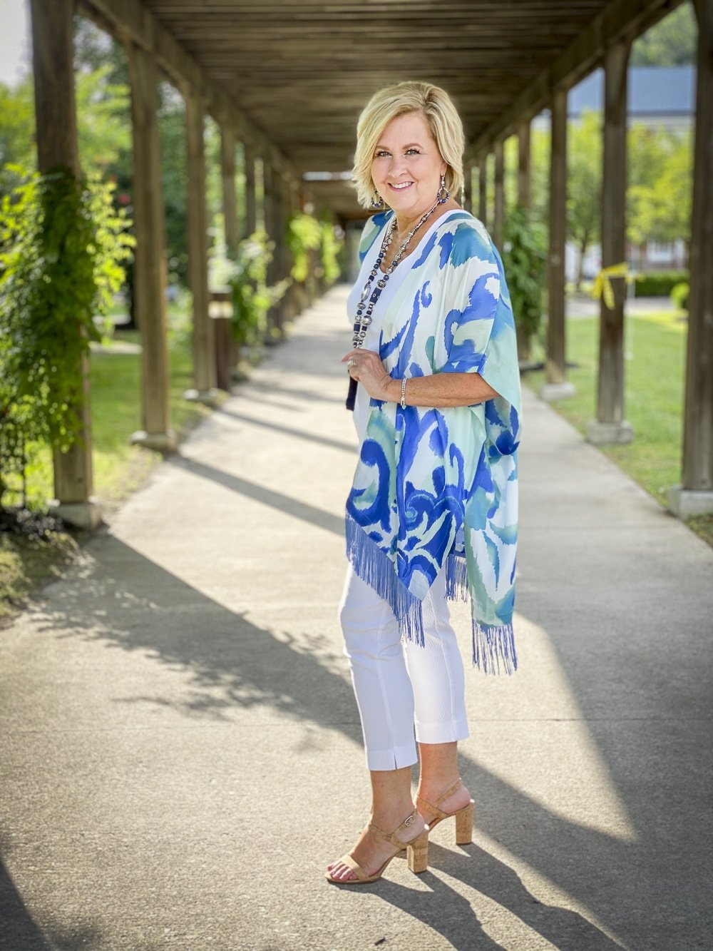 Fashion Blogger 50 Is Not Old is showing the side view of a white tank top, white textured crop pants, and a colorful silk ruana from Chicos with a long navy necklace and bamboo heels