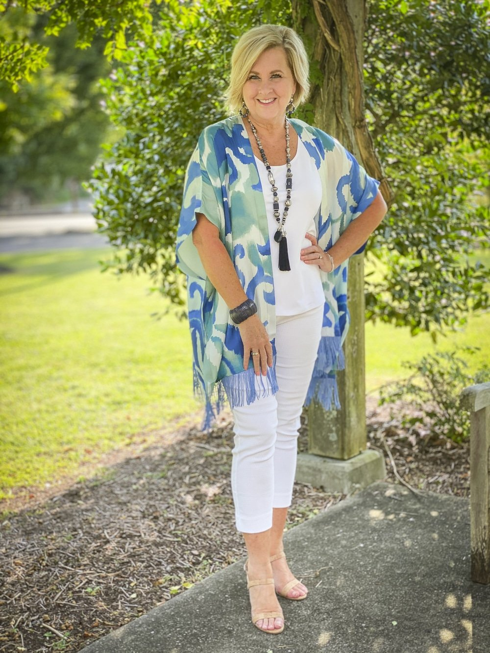 Fashion Blogger 50 Is Not Old is wearing a white tank top, white textured crop pants, and a whimsical silk ruana from Chicos with a long navy necklace and bamboo heels